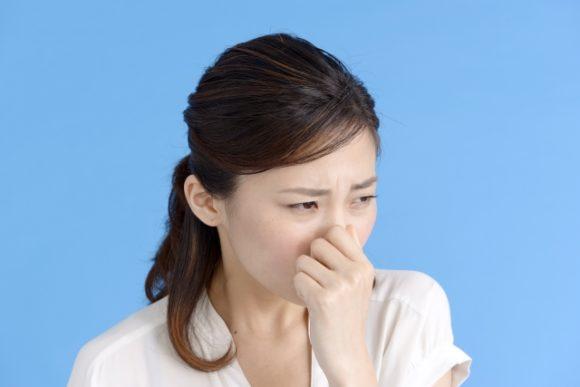 臭くて鼻をつまむ女性