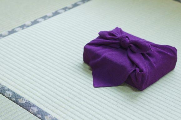 畳の上に紫の風呂敷で包まれた贈り物
