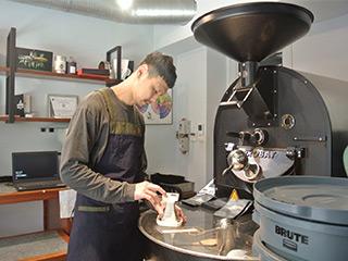 焙煎したコーヒー豆を確認する小楊さんと焙煎機