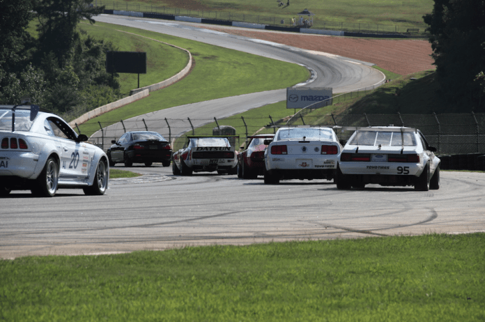 """American Iron and Outlaw Vintage cars head down into """"Gravity's Cavity,"""" the downhill portion of the esses at Road Atlanta."""