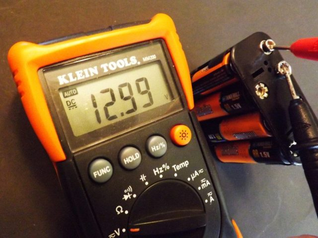 To make sure your battery pack is working to the correct voltage, use a voltmeter and check your readings. Here you can see we are getting a sweet 12.99 volts from our little portable battery pack. Most automotive electronics require between 10 to 15 volts to function.