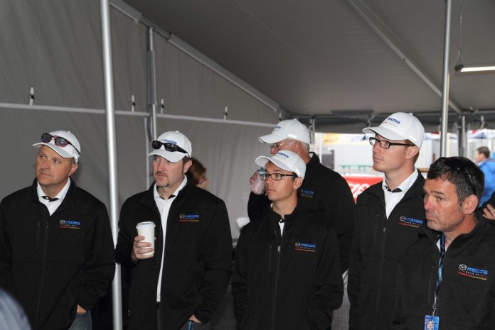Sporting commemorative jackets and hats, drivers (from left) Dan Williams, Michael McAleenan, Tristan Littlehale, Paul Arnold, Matt Powers and Larry Fraser watch a presentation on the development of the global 2016 Mazda MX-5 Cup car.