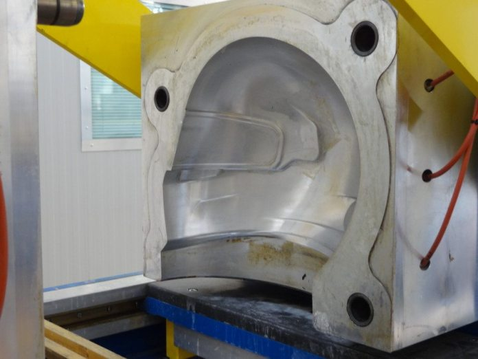 The mold, which is often two-pieces, but can be as many as three or four pieces, closes around the form, which distributes the resin to the right places, forms the shell and applies heat to cure it all in one step.