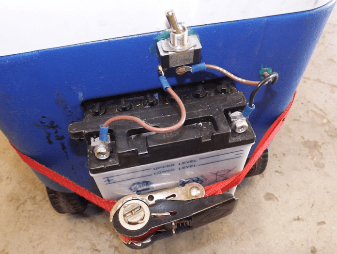 To run this portable cool suit driver's lounge setup, a small lawnmower battery is used for 12-volt power. We wired up an on-off switch to cut power when the system is not in use. This battery is large enough to hold a charge for numerous drivers sitting on deck and cooling off during a long hot race.