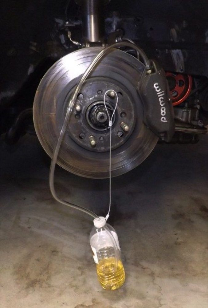 Here you can see the DIY brake bleed catch in action. The small cable hangs the bottle on one of the wheel studs. This keeps the bottle from tipping over and spilling brake fluid all over the place. The plastic tube is just the right length to get to the brake bleed fitting on the calipers.