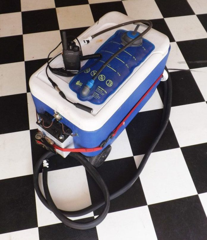 These are the main components for a driver-on-deck driver's lounge: a radio-to-helmet connection with a push-to-talk button, a camel pack with a quick connect tube for a helmet, and a portable cool suit system with a 12-volt battery. All that is needed is some ice, an endurance event and a driver waiting to race.