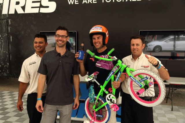 Will Faules, Marc Sanzenbacher and Ryan Flaherty congratulate Bruce Byerly on winning a set of four Toyo Tires — and a toddler bike.