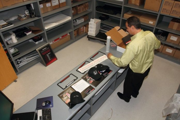 """Vinnie Hernandez packs a up a couple of """"kits,"""" which include all the decals for the racecar and some cool Honda Racing Line swag for racers who sign up with HPD."""