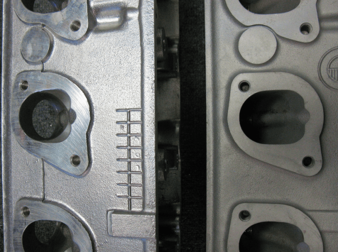 If you look deep into the intake ports of the OEM head (right) and the AMC aftermarket model, which isn't legal, you can see the difference in how far the valve guide protrudes into the throat.