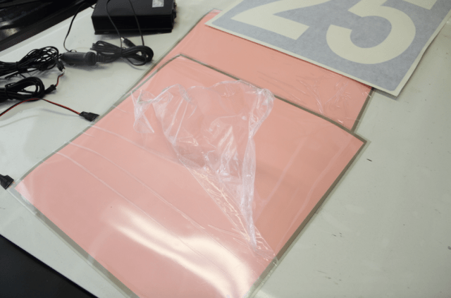 The lighted number panels come with a protective plastic film, which needs to be removed before you can apply the vinyl numbers.