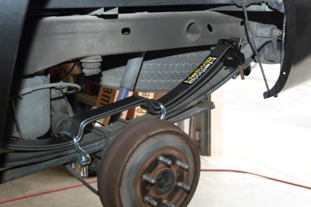 This photo shows several steps combined into one. Lay the Pro Series springs atop the OEM leaves and place the black silencer bushings on the ends. Once everything is in place, position the U bolts as shown. Be sure the long end of the springs are installed at the rear of the truck, and that the offset U bolts angle toward the axle, not away from it.