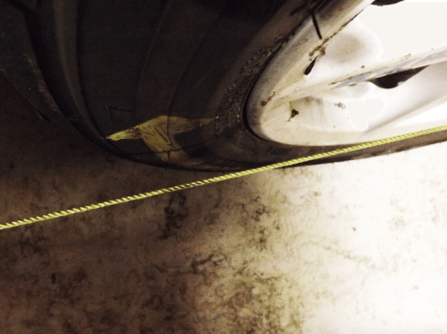 In this photo you can see that the string taped to the front of the front tire is touching the edge of the rim at the front, but is not touching the edge of the rim at the rear of the wheel. This indicates toe out alignment. If the string on the other side of the car is touching both the front and rear of the rim, then this would be the side to make the adjustment on.