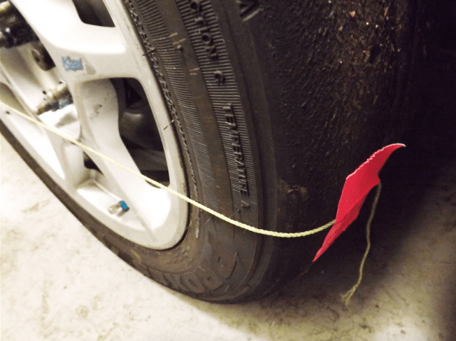 To determine which direction to adjust toe, or which side of the car to adjust it on, it helps to use strings on the sides of the tires. A simple solution is to use some duct tape to tape the string at hub height to the front of the front tire and at the rear of the rear tire.