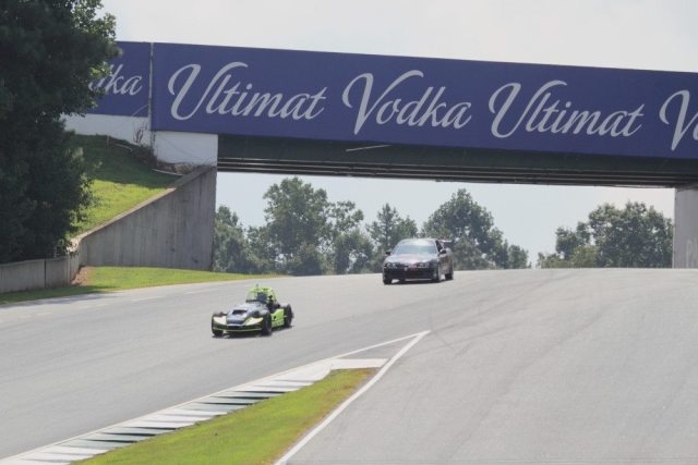 Use the yellow, red and white sign to find a good position going under the bridge and set up for the approach to Turn 12. Turn 11 goes from uphill out of Turn 10B to downhill into Turn 12.