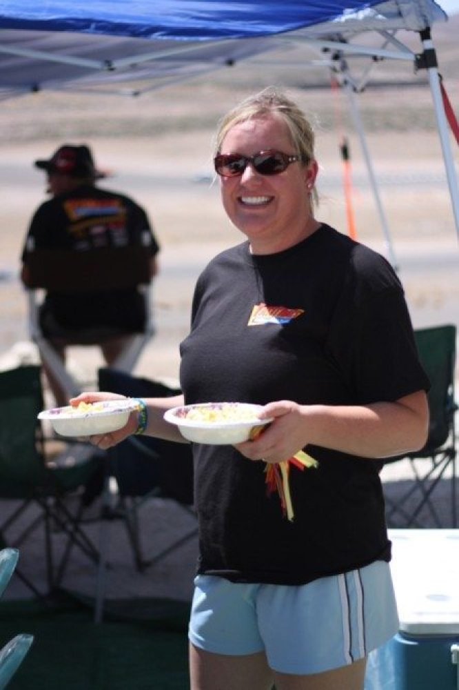Happy wife, happy life — and happy crew at the racetrack. Mrs. Krider happily hands out a much-needed lunch to the pit crew. She is smiling because she made it in her new motorhome, as opposed to under a sweltering tent.