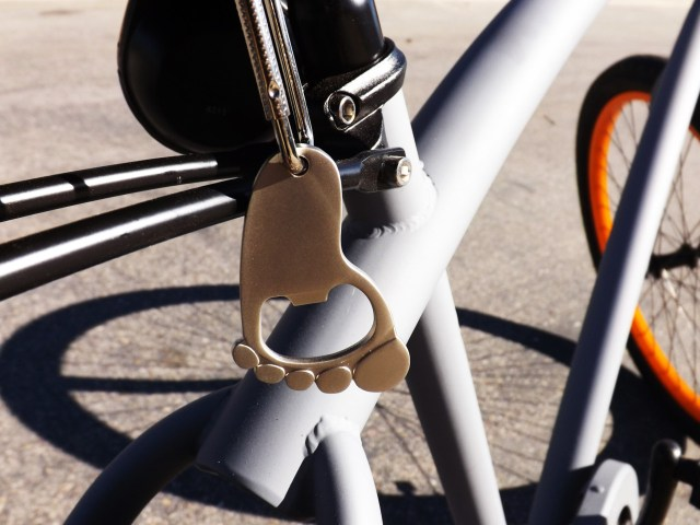 "No craft beer can be consumed until this little helpful opener gets the tops popped off. A carabineer under the seat makes for ease of access to open some brews. The inspiration for this right foot bottle opener on our bike is ""pedal to the metal."""