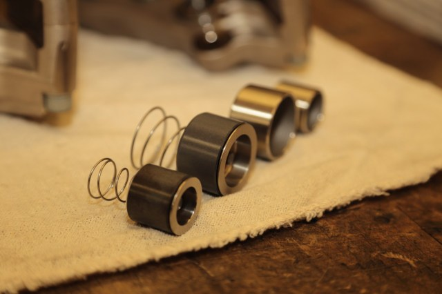 Because the Mini will be use for Time Trials and racing, the calipers will be fitted with special pistons. They have an additional insert, which helps prevent heat transfer from the pad through the piston to the fluid. Note the standard pistons in the background.