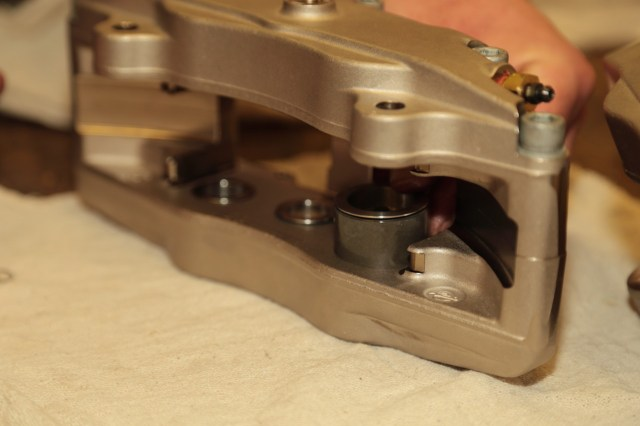 Bushman inserts the piston into the caliper bore. Note how the Wilwood caliper uses different diameter pistons, which helps prevent pad taper in heavy-braking applications.