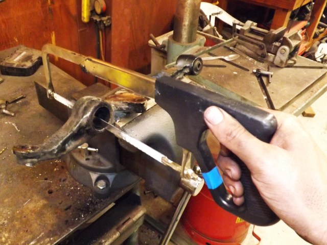 If you are spending 10 minutes and are wearing a hole through your shoulder trying to cut a one-sixteenth-inch-thick piece of metal, then you need a new blade. When you replace the blade, insert it into the lower control arm before you attach it to the saw. Now you can cut the sleeve.