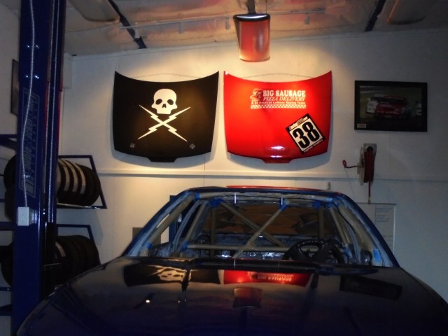 This space was created to maintain racecars, but it also was built as a man's clubhouse to hang out, enjoy some beers and do some bench racing. We hung hoods from previous racecars and added track lighting.