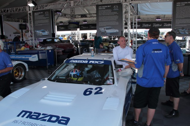 Driver Jeremy Barnes talks with the all-volunteer crew about the RX-7 GTO after a session on track.