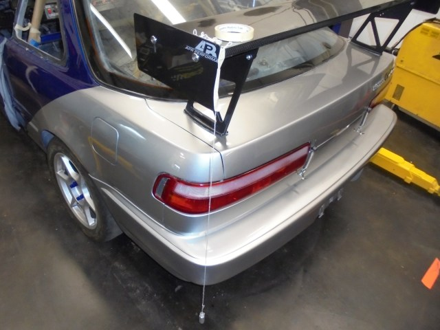 For rear downforce we added an APR Performance wing to the trunk lid. The rules in Honda Challenge specify that no portion of the wing can protrude outside of the stock bodyline. To ensure we were within the rules set, we used a plumb bob taped to the wing to mount.
