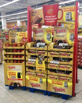 Rot-gelb leuchtender Stand von Twix (Mars) mit Gratis-Kaffeetassen und Gewinnspiel.