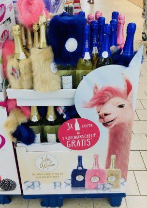 """Ein Display von """"Jules Mumm""""-Sekt mit Gratis-Lamafell-Kühltaschen."""