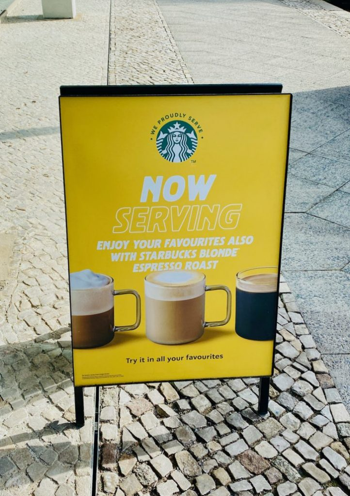 Schild Now Serving Starbucks Coffee