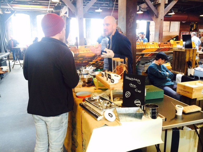 Am Naschteig-Stand in der Fabrik steht Besitzer Marc Freitag hinter dem Verkaufstresen und erklärt einem Kunden, was es mit dem Teig zum Naschen auf sich hat.,