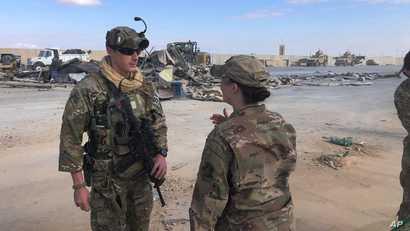 U.S. Soldiers stand near the site of Iranian bombing at Ain al-Asad air base in Anbar, Iraq, Monday, Jan. 13, 2020. Ain al-Asad…