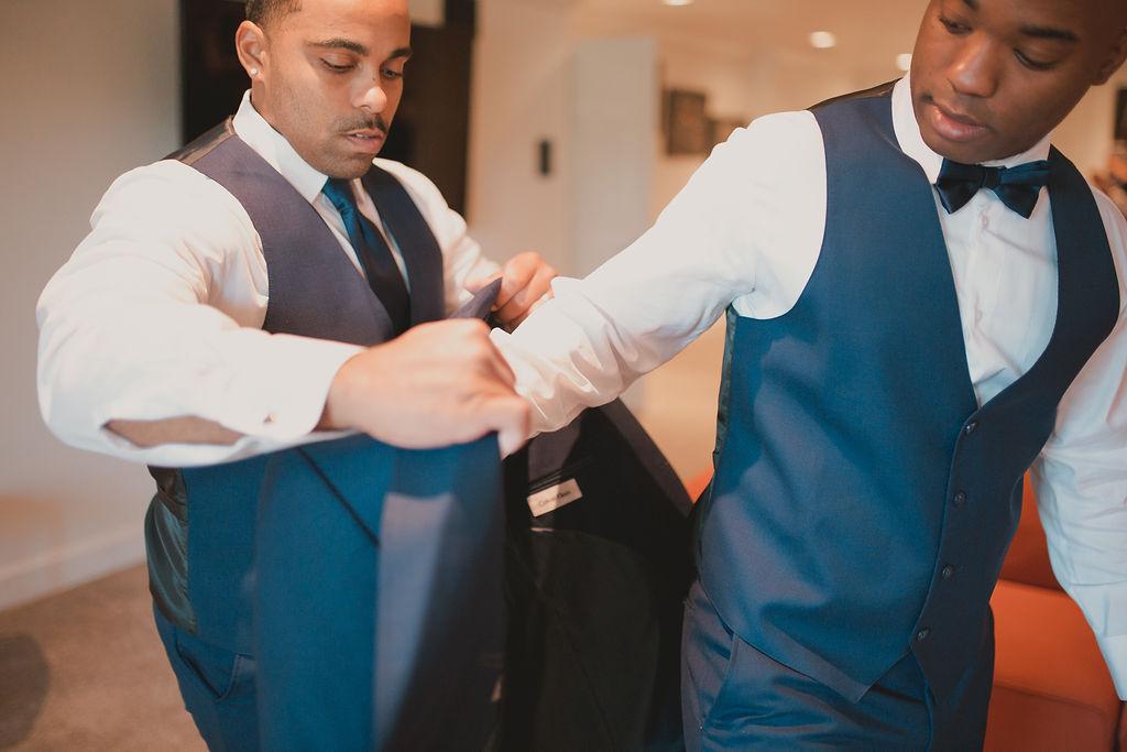 Groomsman helping groom put on tuxedo jacket