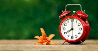 Daylight savings, spring forward concept - red alarm clock and a