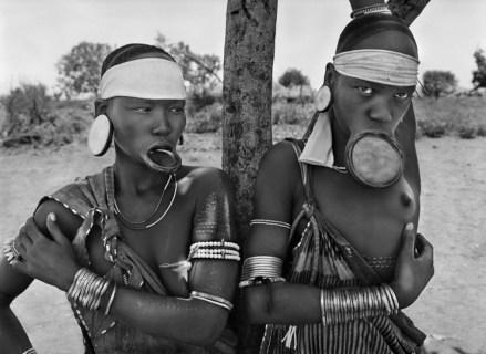 Mursi de Argui, pueblo del Parque Nacional de Mago, Etiopía, 2007 | Las mujeres mursi y surma son las últimas mujeres del mundo con platos en los labios. Ningún antropólogo ha podido explicar el origen y la función de esta práctica. Algunos piensan que esta deformación corporal, antiestética a los ojos de los traficantes de esclavos, fue impuesta por los hombres para proteger a sus mujeres. Sólo aquellas pertenecientes a una casta alta tienen derecho a llevar estos platos.