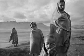 Campamento de Korem, Etiopía, 1984 | Unos refugiados, víctimas de la sequía en el Sahel, se protegen con mantas del viento y del frío de la mañana.