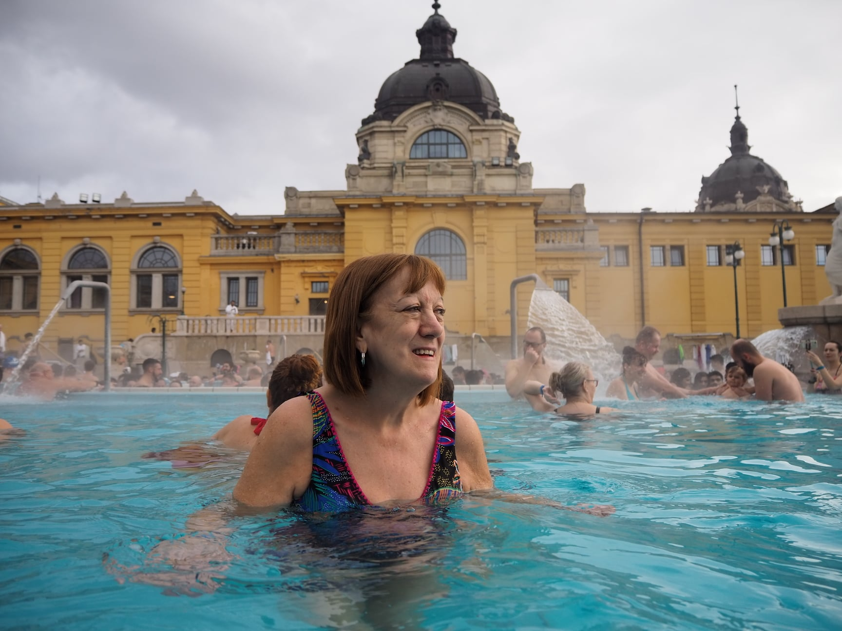 mum in the thermal baths looking into the distance, with the building behind her