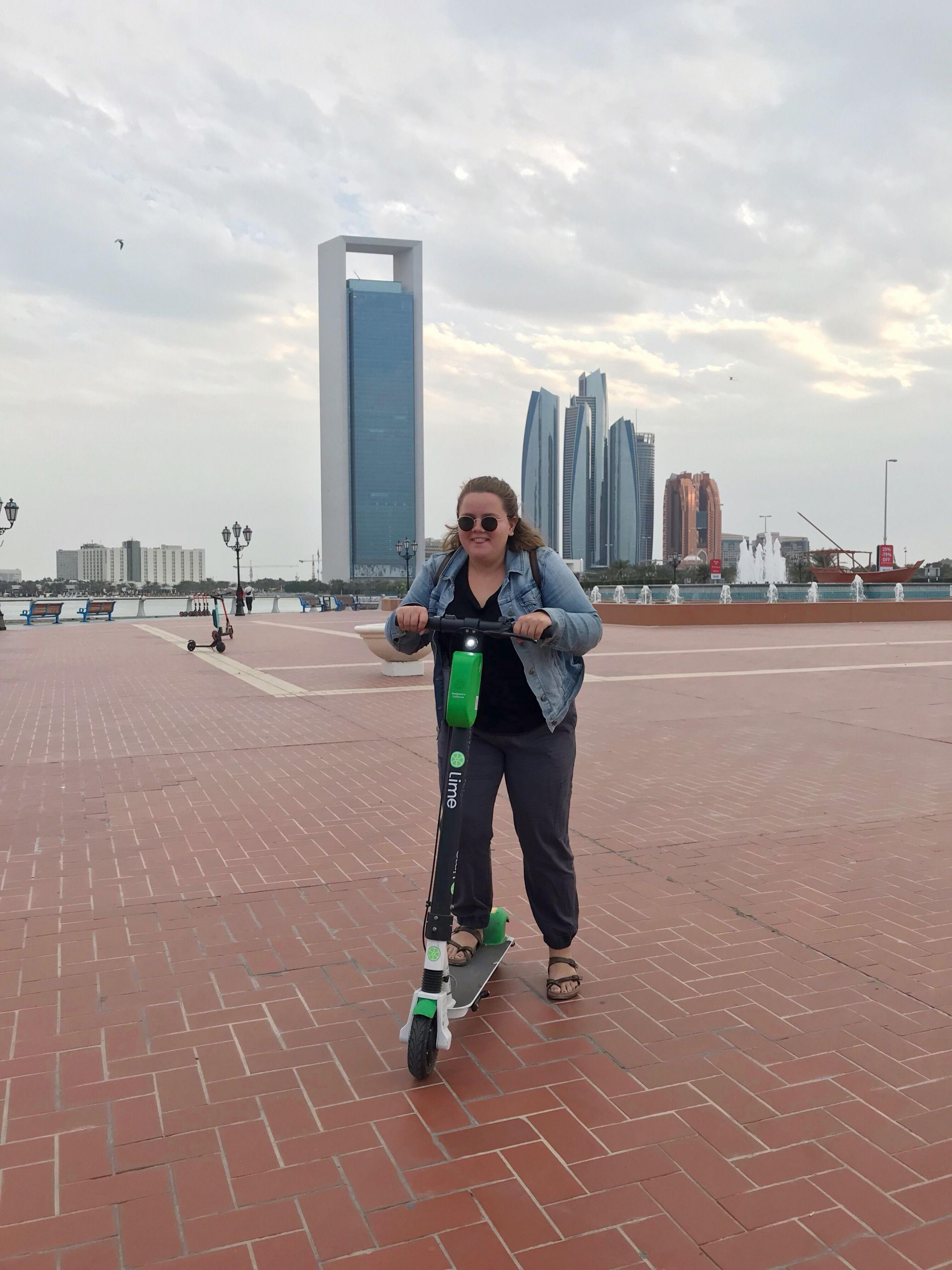 Riding scooters in Abu Dhabi with buildings behind