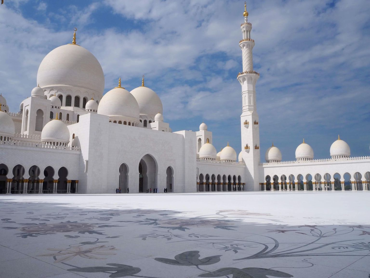 landscape photo of the outside of sheikh zayed mosque with the blue sky and sun reflection