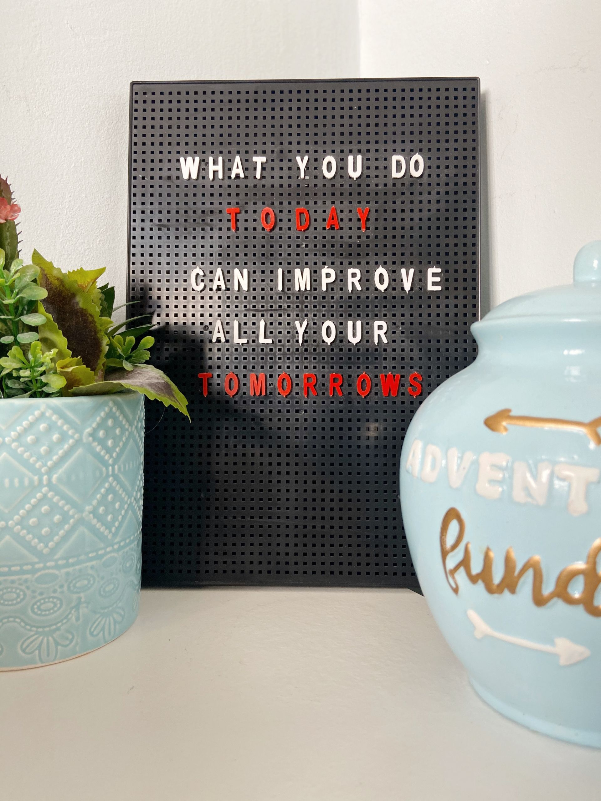 quote board with savings jar and plant