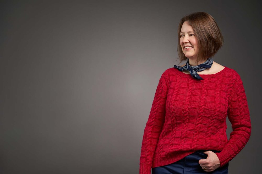 Smiling Jen modelling the strawberry red Unite sweater with indigo jeans and accessorised with a navy neck scarf.  Image credit: Jesse Wild