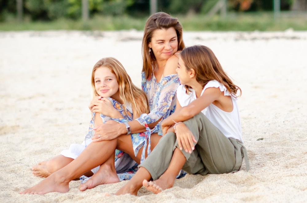 mother poses on the beach with her daughters