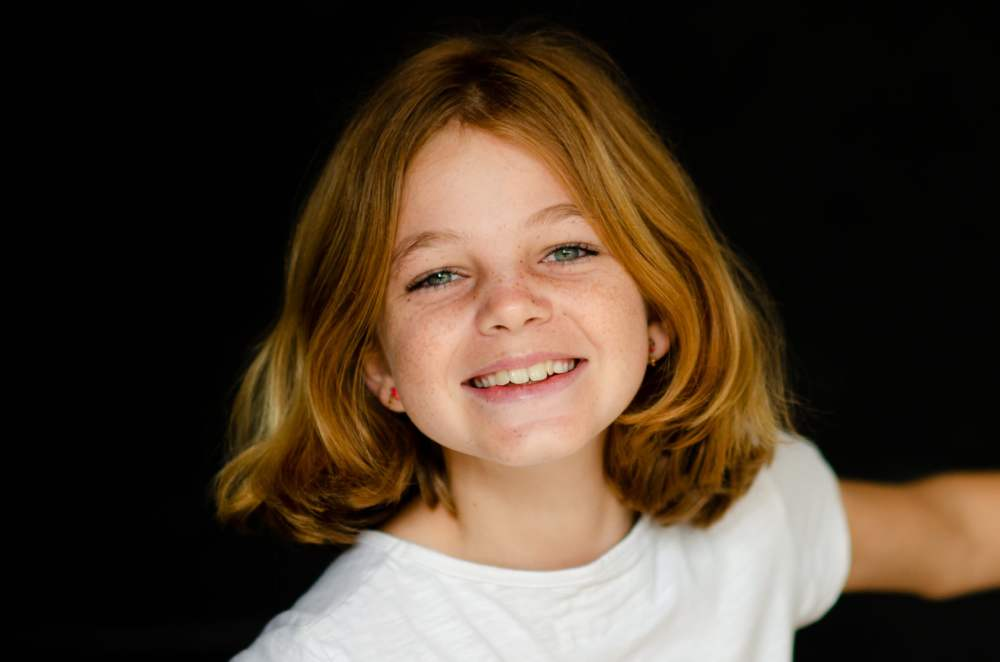 a young girl with red hair smiles for a photo against a black backdrop