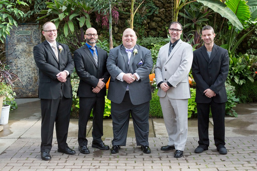 Groom and groomsmen posing together on in the Belle Isle Conservatory
