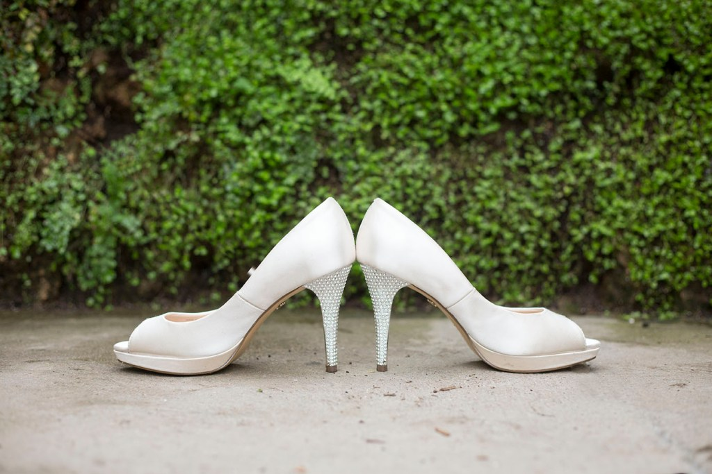Wedding shoes in front of boxwood