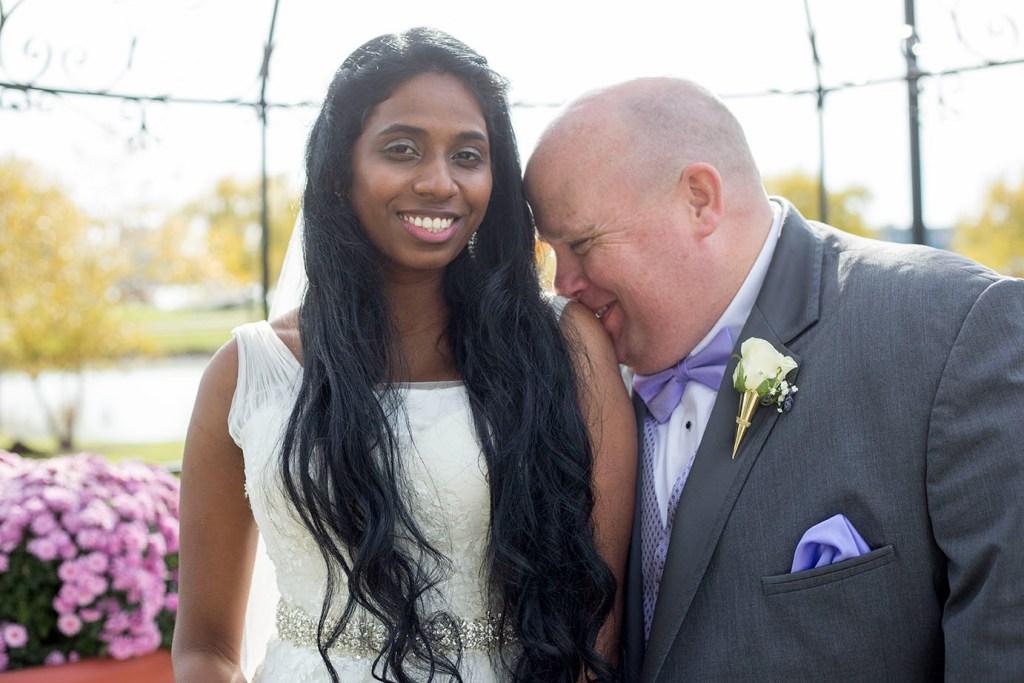 Groom kisses bride's shoulder under gazebo on Belle Isle
