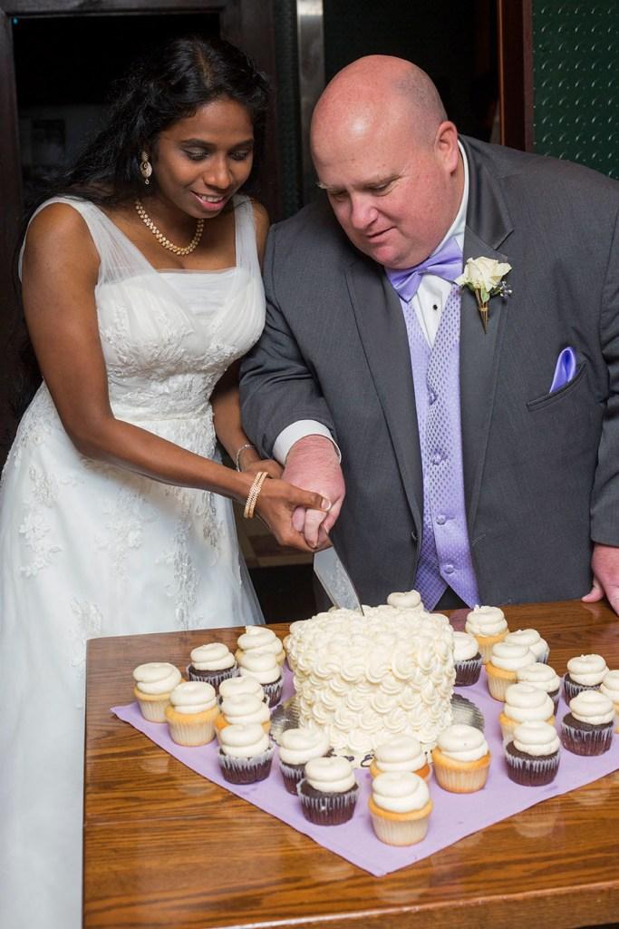 Wedding couple cut the cake at their Detroit wedding