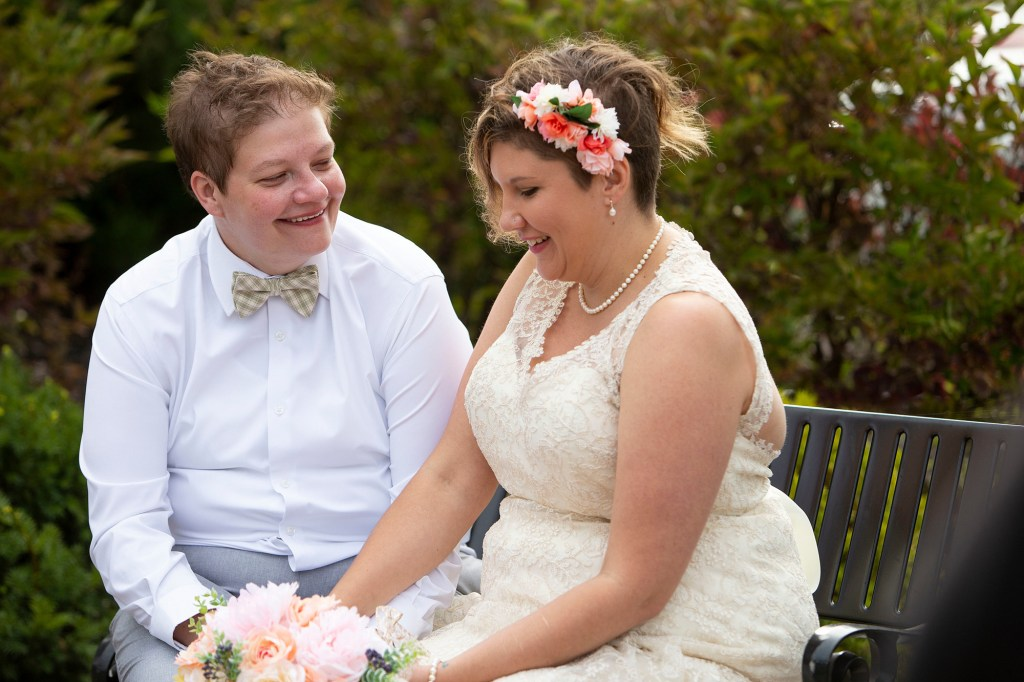 Michigan lesbian wedding couple sit together outside after their first look