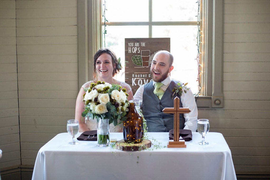 Corey and Rachel sitting at the head table of their Chelsea wedding