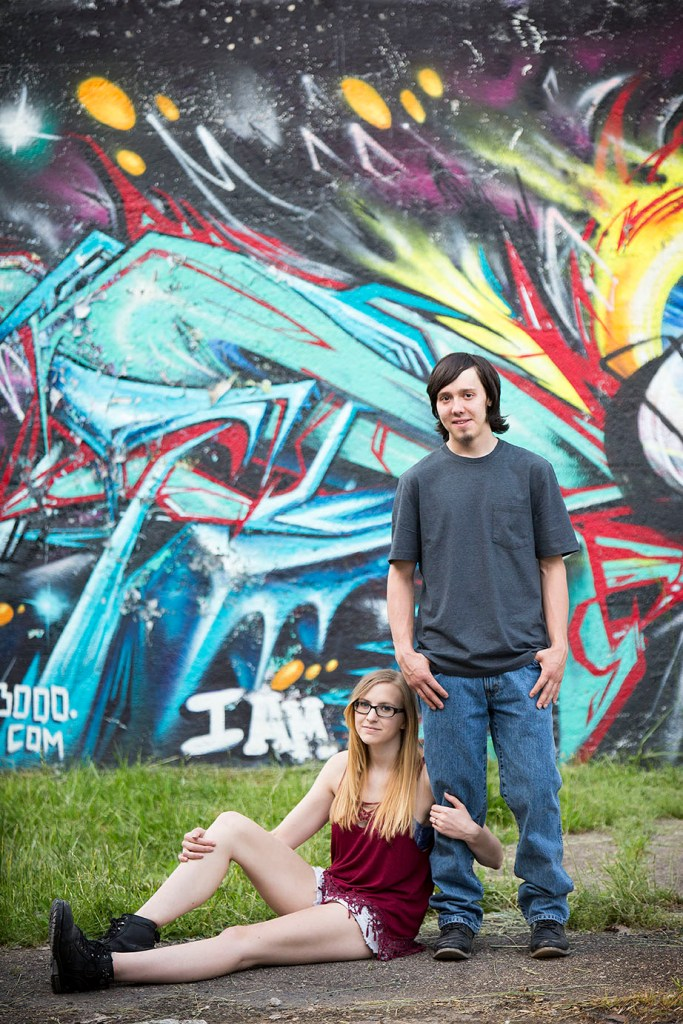 Detroit urbex engagement session cuddling up in front of graffiti