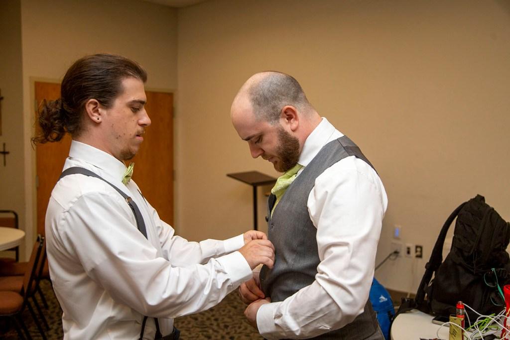 Best man helping the groom get ready